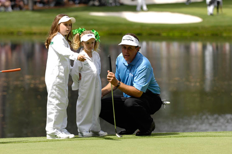 Phil lines up a putt with his caddies in 2008
